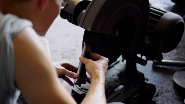 asiatischer mann schleifen ein bügeleisen in schmiede-werkstatt - einzelner mann über 30 stock-videos und b-roll-filmmaterial