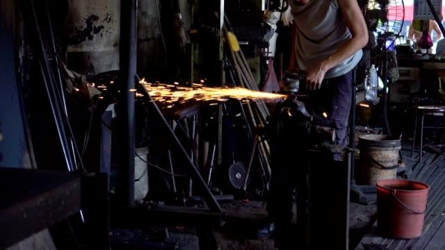 Asian man grinding an iron in Blacksmith workshop