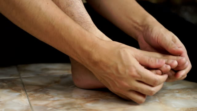 asian man hand massage on his feet - human foot stock videos and b-roll footage