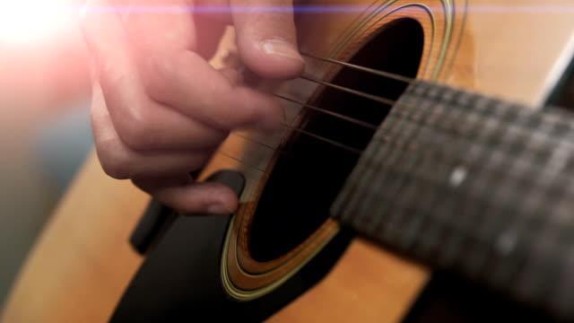 vídeos de stock, filmes e b-roll de mão de homem asiático tocar violão - dedilhando instrumento