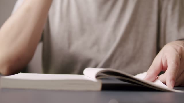 asian man hand reading a non-fiction book while staying at home. he turning page of learning book . adult man using his finger pointing on a book. - open book stock videos & royalty-free footage
