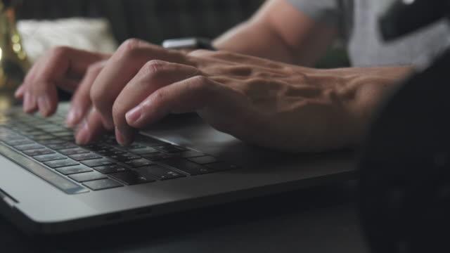 vidéos et rushes de asian man main tapant ou la recherche sur l'ordinateur portable tout en rester à la maison. gros plan de la vitesse des doigts humains tapant e-mail à partenaire d'affaires. - écrivain