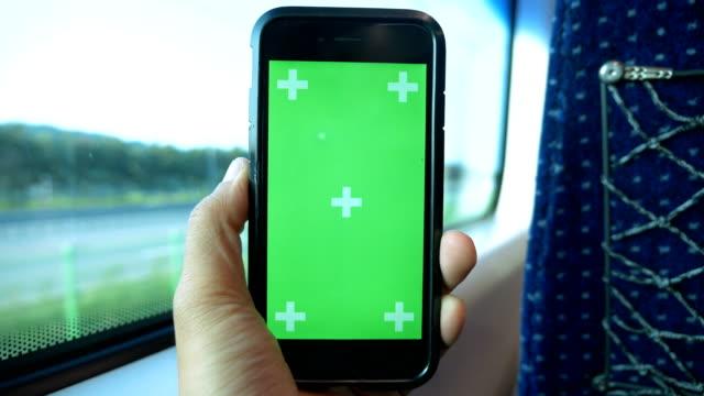 vídeos de stock, filmes e b-roll de homem asiático portátil verde um telefone inteligente tela no trem, negócio de ir, entretenimento, coreia. conceito: para viajar pelo mundo, férias, férias. - modelo web