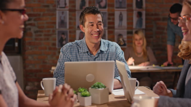 Asian man having a meeting with two women behind his office desk