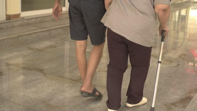 アジアのシニア女性がトレーニングを歩くのを手伝うアジア人男性 - 介護点の映像素材/bロール