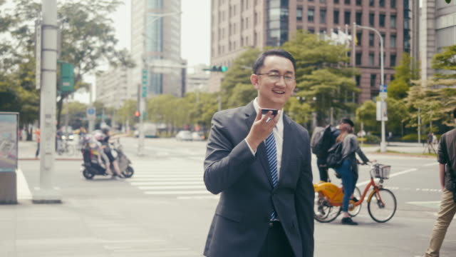 asian man holding a conference call on the street - conference phone stock videos & royalty-free footage