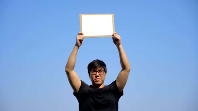 asian man holding white borad into sky - banner sign stock videos & royalty-free footage