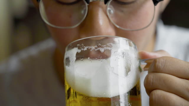 vídeos y material grabado en eventos de stock de hombre asiático en anteojos bebiendo cerveza - cerveza
