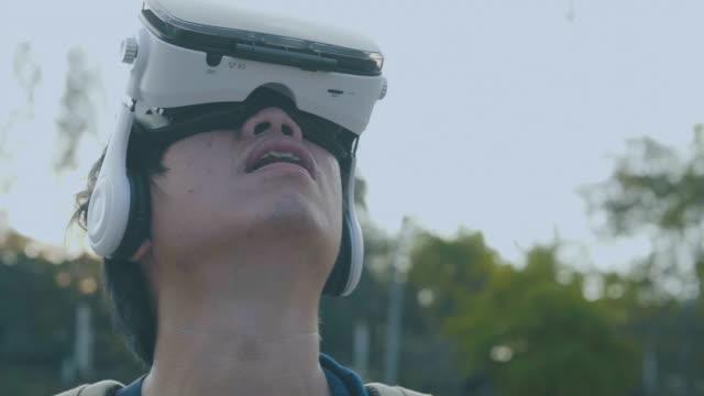 asiatischer mann in vr brille controlling drohne - schutzbrille stock-videos und b-roll-filmmaterial