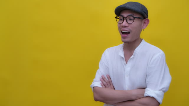 asian man in white shirt wearing eyeglasses and a cap smiling in yellow background copy space - yellow background stock videos & royalty-free footage