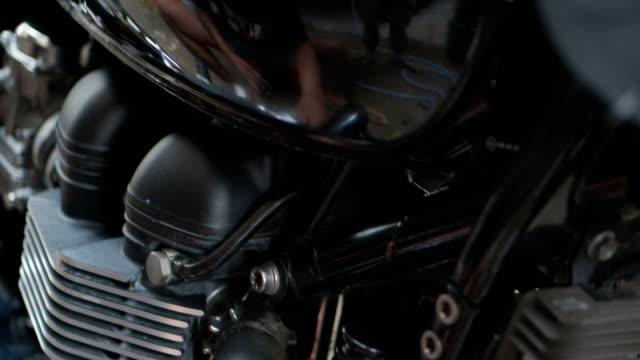 asian man is cleaning his classic motorcycle at home. - motorino video stock e b–roll