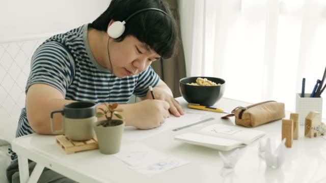 Aziatisch mens is het tekenen en schrijven van zijn werk tijdens het luisteren muziek met positieve emotie en ontspanning op zijn kamer