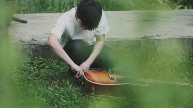 Asiatischer Mann bereitet Gitarrengurt mit Gitarre sich vor dem Abspielen von Musik