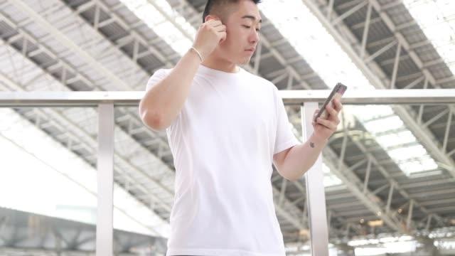 vídeos y material grabado en eventos de stock de un hombre asiático está usando audífonos inalámbricos - 20 a 29 años