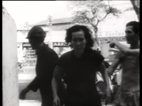 asian man leading distressed woman past camera / 1960's / saigon / no sound - vietnam war stock videos & royalty-free footage
