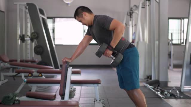 stockvideo's en b-roll-footage met aziatische man tilt halters op, voor de spieren van zijn armen en rug - menselijke arm