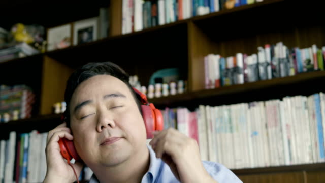 asian man listening to music - 40 44 years stock videos & royalty-free footage