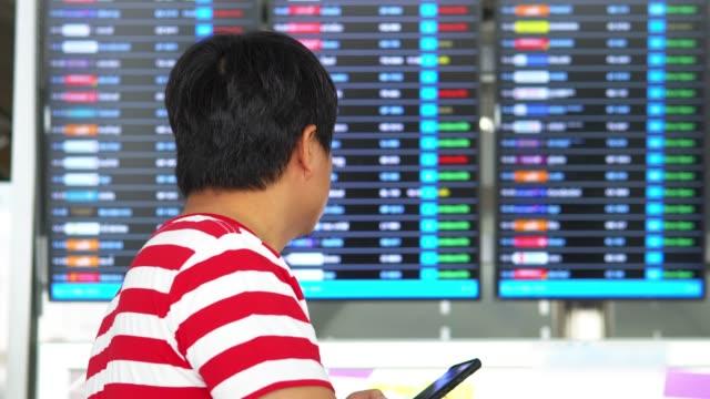asiatischer mann mit blick auf abfahrtsort. - flugpassagier stock-videos und b-roll-filmmaterial