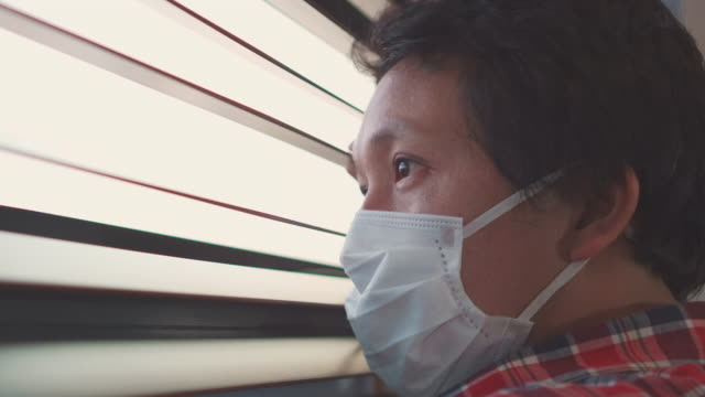 asian man looking through window self-quarantine for coronavirus - memories stock videos & royalty-free footage