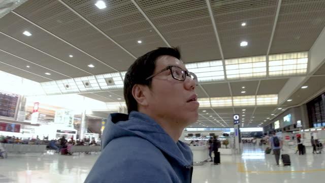 アジア人男性は空港で失われました。 - 見つける点の映像素材/bロール