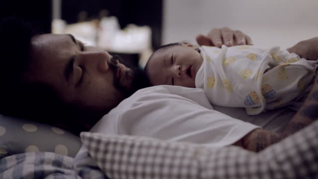 asian man lying on bed and holding sleeping newborn baby. - single father stock videos & royalty-free footage