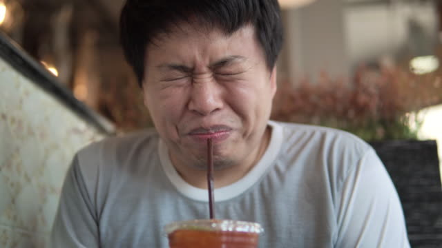 asian man makes faces grimacing when eating lemon tea. - juicy stock videos & royalty-free footage