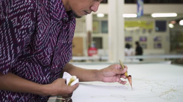 asian man making batik in the workshop - batik stock videos and b-roll footage