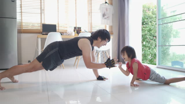 asian man man bodyweight training with little boy at home during covid-19. - bodyweight training stock videos & royalty-free footage