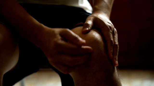 asian man massage on his knee pain and feeling bad - injured stock videos & royalty-free footage