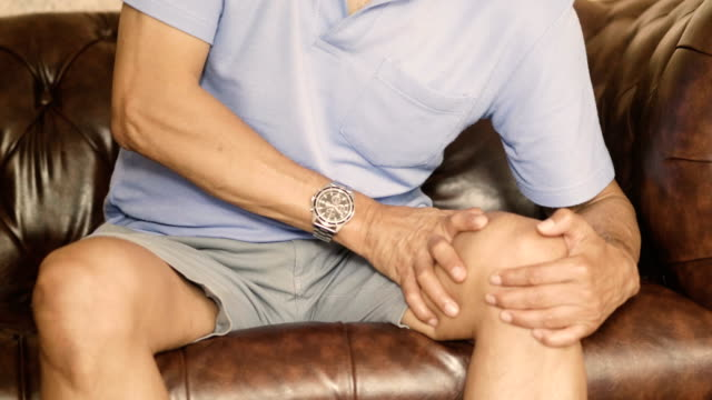asian man massage on his knee pain - cartilagine video stock e b–roll