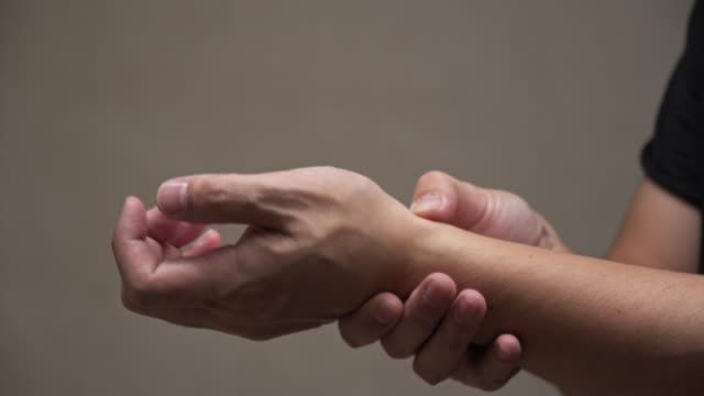 asian man massage on his wrist hand pain - wrist stock videos & royalty-free footage