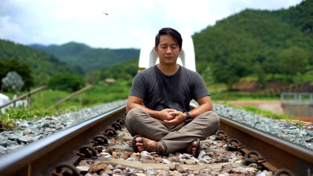 Asian Man Meditates on a Railway in sitting pose