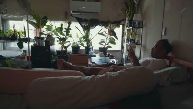 vídeos de stock e filmes b-roll de asian man no work to do using smart phone on the bed. - povo tailandês