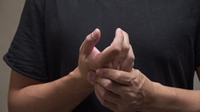 asian man on black shirt feel pain on his finger.muscle pain, health care concept. - pain stock videos & royalty-free footage