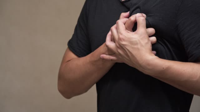 asian man on black shirt feel pain on his heart.heart attack, health care concept. - chest torso stock videos & royalty-free footage