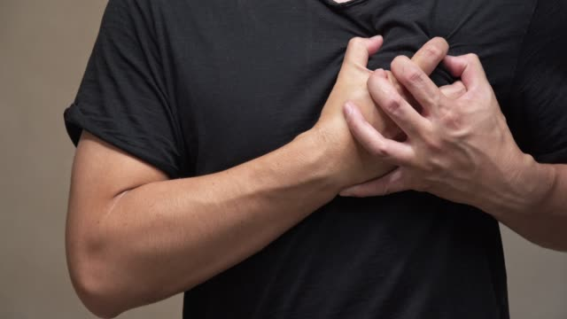 asian man on black shirt feel pain on his heart.heart attack, health care concept. - myocardium stock videos and b-roll footage