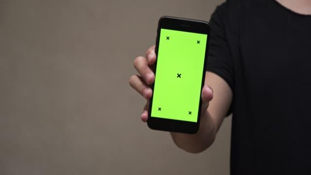 vídeos y material grabado en eventos de stock de hombre asiático en camiseta negra sosteniendo smartphone con pantalla verde y apuntando en la pantalla. - número 10