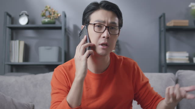 asian man on conversation talking and chatting on mobile phone about his important project with his partner while sitting on the sofa in the living room at home. telecommunication and social connection technology concepts. - asking stock videos & royalty-free footage