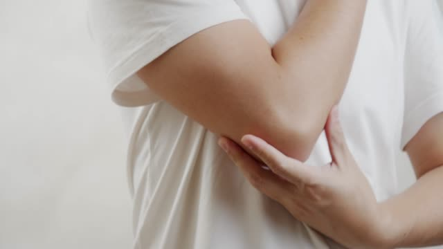 asian man on white shirt feel pain on his elbow.muscle pain, health care concept.