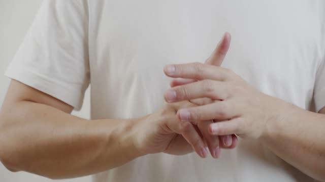 vídeos de stock e filmes b-roll de asian man on white shirt feel pain on his finger.muscle pain, health care concept. - artrite