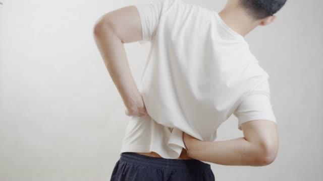 vídeos de stock, filmes e b-roll de homem asiático na camisa branca sentir dor em sua lombar. dor de músculo, conceito dos cuidados médicos. - baixo posição