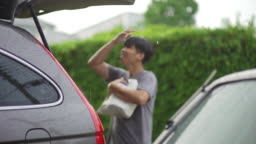 Asian man opening the car trunk and holding shopping bag among the rain over his body in the evening