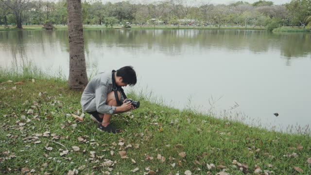 Asian man photographer is taking a picture at public park