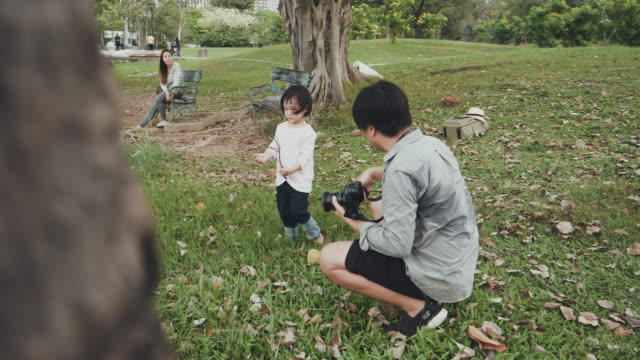 Asian man photographer is taking a picture of him family at public park
