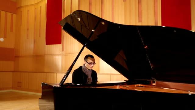 asian man play piano - ピアノ点の映像素材/bロール