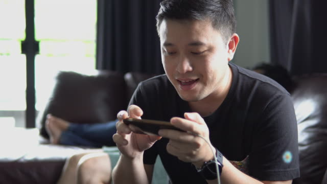 asian man playing game online on smartphone. - charging sports stock videos & royalty-free footage