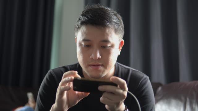 スマートフォンでオンラインゲームをしているアジア人の男性。 - マッチ点の映像素材/bロール