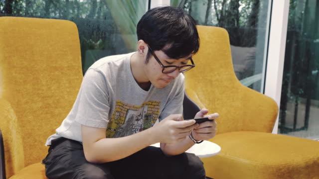 アジア人の男性がスマート フォンでゲームをプレイ - 通信点の映像素材/bロール