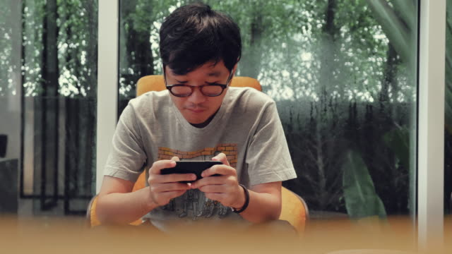 asian man playing games on smartphone - leisure games stock videos & royalty-free footage