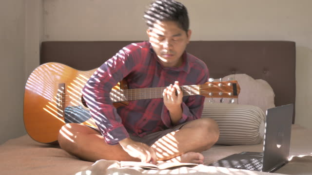 asian man playing guitar for relaxation on bed, concept day in the life fever covid-19 quarantine - day in the life stock videos & royalty-free footage
